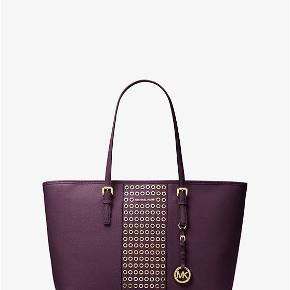 Jet Set Travel Grommeted Saffiano Leather Tote.  You can fit a laptop and more items.  It's travel friendly and in excellent shape.  It also comes with a duster bag.
