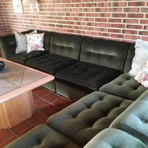"""Vildt flot og velholdt grøn sofa, der enten kan anvendes som hjørnesofa (som på billedet) eller opdeles i mindre sofagrupper, da sofaen er sammensat af moduler. Hynderne er vendbare.  Den er ikke """"siddet"""" i stykker, skummet er ikke faldet sammen og der er ingen huller/tegn på slid. Skummet er fast og ikke løst skum. Alt i alt en velholdt sofa, der har mange år tilbage i endnu.  Som sofaen står nu, så måler den i siddehøjde 40 cm. og 70 cm. op til ryglænet. Den er 3,15 lang, i bredden 80 og dybden (den der går ud i rummet) er 2,30  Sofaen er ca. 20 år gammel, og stammer fra en møbelfabrik, der ikke eksisterer længere.   Står i 9300 Sæby, hvor den også skal afhentes.  AFSLAG GIVES VED HURTIG AFHENTNING  KUN SERIØSE HENVENDELSER"""