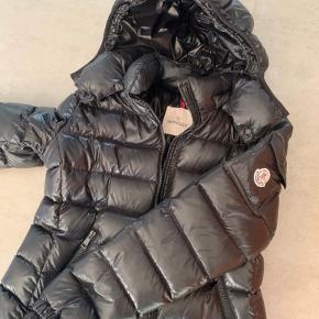 """Sælger min fine moncler jakke, da den desværre er købt for stort. Jakken fejler intet udover den lille """"tegneserie"""" inden i sidder lidt løst, men det er ikke noget man ser når man har den på - og den fejler intet uden på. Den er str 2 og er i modellen bady"""