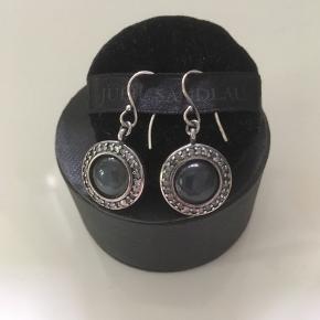 Fine ørenringe fra Julie Sandlau i oxideret sølv og med en flot mørkegrå sten ( hæmatit / månesten ) omkranset af små, fine sten.   De er kun brugt få gange.