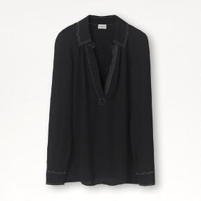 Dette er en skjorte, som alle burde have i deres garderobe. Den lave, åbne hals gør den frisk og sjov, mens kontraststikninger hele vejen igennem leder tankerne hen på arbejdstøj. Det er en top perfekt til et professionelt look, der dog også vil være smart til en aften i byen eller en hyggelig weekendtur: Den er perfekt til enhver lejlighed! Almindelig pasform Kontraststikninger ved kraven, ærmerne og halsen 100% viskose Skånsom maskinvask  700 pp Bytter ikke  Nedsat til 600pp