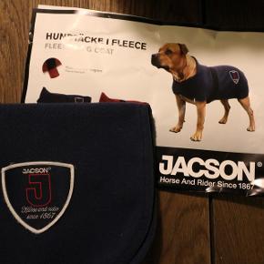 """Lækkert og blødt """"Jacson"""" hundedækken som er lavet i tætvævet fleece. Dækkenet varmer og er velegnet til når det er køligt, når hunden er våd og skal transporteres, som pause-dækken til hundetræning, eller til at have på under regnjakken. Lukkes med velcro. Indvendig etiket med plads til hund+ejers navne. Kan maskinvaskes på 40 grader. Str. 40 cm (rygmål)  Kun brugt 2 gange.  - Spørg for flere billeder :) Kan prøves og hentes i 2800 eller sendes mod betaling."""