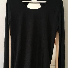 Rigtig fin og elegant bluse/top med åben ryg fra Moss Copenhagen.  Sort/mørkegrå. Har kun været brugt ét par gange og bærer intet præg af dette. En str. M, men kan sagtens bruges af en str. XS og S. (Er selv en str. S, se billede 3)  Materiale: 78% viskose, 17% uld, 5% elastan