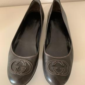 Gucci ballerina i læder med GG logo på snuderne. Sortgrå farve med beige syninger rundt i kanten og i logo'et. Brugt få gange. Købt her på TS, men har aldrig fået dem brugt. Ingen skader eller slid på skoene.