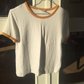 Hvid t-shirt med karrygule detaljer i ærmer og hals fra Forever 21. Er en lillebitte smule cropped🌱