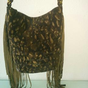 Tasken er i ruskind og måler: 25 cm x 25 cm.
