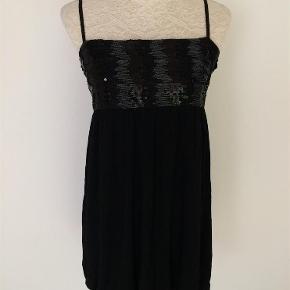 Blød behagelig kjole i bomuld, spandex. Bryst stykket har palietter og sølv tråd. Elastik på ryggen. Inder foer som er syet sammen med yderside og giver en poset effekt. Regulerbar elastik stropper.  Længde som på foto 83. Bryst 38-50 og mere til, da den kan give sig meget.   Kig forbi mine annoncer 😊 Giver altid mængderabat  Kort kjole med palietter/ Den lille sorte Farve: Sort