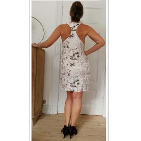 Bytter ikke.  Købspris kr. 1.300,-. Elegant kjole fra Designers Remix str. 38. Kjolen er let figursyet, har for, lynlås i den ene side, 33 cm lang, draperet vandfald ved halsen. Størrelsesguide str. 38/M: Bryst mål 92 cm. Talje mål 75 cm Hofte mål 98 - 100 cm For og bag stykke målt ved bryst linjen, 96 cm. Længde fra skulder og ned 81 cm. Målt på ginen. For og bag stykket målt ved hofte linjen 102 cm. For og bag stykket målt ved talje vidde 88 cm. Yderstof: 81% Tencek, 19% Polyamid For: 100% Bomuld. Farven: Pastel cream, rosa, lys brun/grå, se billederne, det er lidt svært at beskrive. Kjolen fremstår i virkelig pæn stand. Har været brugt få gange. Kommer fra et ikke ryger hjem. Hænger i dragt pose.