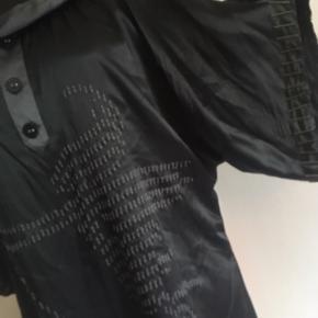 """★ NY SMUK HAWALESCHKA SILKEKJOLE M. MESSING- OG BRODERI-DETALJER ★  En rigtig smuk tunikakjole i 100% sort silke med grå silkekrave og grå detalje på brystet med 3 påsatte silkebetrukne knapper (til pynt - kan ikke åbnes). Nedadtil er med løs tråd """"broderet"""" et grafisk mønster af, hvad der kan anes som værende en figur med bue - måske Amor?   Tunikakjolen har store vidde ærmer med aflange runde messing-silke påsyet langs ærmekanterne - en ret speciel detalje! Silken smyger sig let, når man har den på, så den er virkelig behagelig og blød.  Tunikakjolen er en str. 44, men vil kunne passes af både en M og L, og pasformen er vid oversize. På mig selv går den et godt stykke ned over numsen - til midten på lårerne, og jeg er 158 cm høj.   100% ægte silke samt messing. Anvisningen oplyser: Undgå vask eller skånsom rensning.  Tunikakjolen er helt ny og aldrig brugt. Nypris kr. 999,-. Se evt. denne webshop for samme model i lilla: https://www.miinto.dk/p-20097602-kjole  Pris ved afhentning i Nordsjælland ellers + porto."""