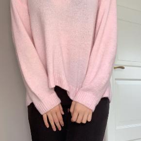 Jeg sælger denne meget fine lyserøde strik. trøjen har en dyb v udskæring, som også fungere rigtig  fint med en t-shirt, der dermed kommer til syne i kanten.