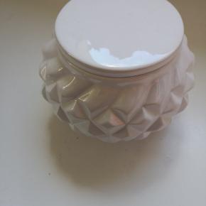 Butiks pris 259,-  Flot hvid keramik krukke designet med et quilted look og låg fra Lene Bjerre. Denne krukke måler H8xØ11 cm. og kan indeholde 32 cl. Brug denne Oliva krukke til trendy opbevaring for et mere karakteristisk og personligt udtryk. Brug den for eksempel til vatrondeller, vatpinde eller til lige hvad du har lyst til. Hos Lene Bjerre har vi skabt et bredt sortiment af unikke krukker, hvor både funktionalitet og design er i fokus. Vi præsenterer derfor en palette af flotte krukker, for at sikre, at der er noget for enhver smag.