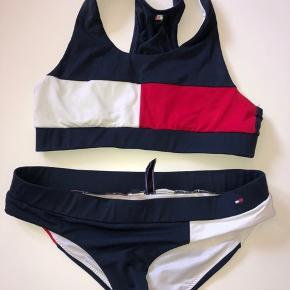 Fin blå, rød og hvid Tommy Hilfiger bikini Brugt én sommer  Cond: 6,5/10 Np: 350kr Mp: Byd   Den er i god stand, så den kan sagtens bruges.  Sender gerne Byd realistisk    Så skriv hvis du er intra eller for flere billeder