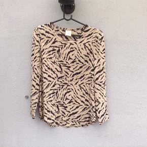 Flot bluse sort/camel i 93% silke, 7% spandex. Brystmål ca. 52X2 cm, længde 68 cm bagpå.