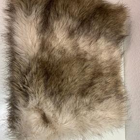 Fin kunstpels fra H og M lavet som et rør i beige, grå og hvide nuancer med gråt foer. Aldrig brugt og venter blot på en ny ejer☺️