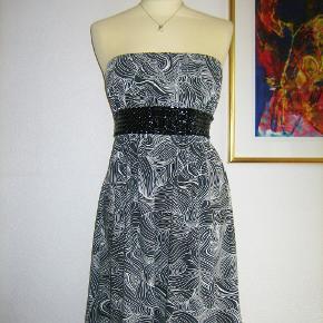 """FEST  -  FEST  -  FEST Farve: sort-hvid-grå  Flot og festlig kjole, som er stropløs og med lynlås i siden. Kjolens forside har et flot og dekorativt """"bælte"""", som sidder fast på kjolen. Bæltet er af sort lak, som er flettet.  Brystvidde: 43-50 cm x 2 (på grund af stoffets elasticitet) Længden målt fra under armen og til nederste kant: 70 cm.  Ingen byt, og prisen er fast"""