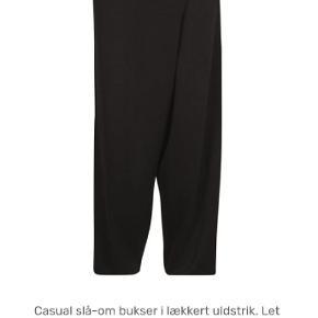 Helt nye luksus-designer-bukser fra Eva og Claudi. Meget lækker kvalitet, unikt snit med et overslag / bredt læg foran og bred (7 cm) lidt elastisk linning (43x2). (Læs beskrivelse nederst på billede 1) 50 %uld, 50% polyester.  Se også mine andre annoncer. Rabat ved køb af flere ting.