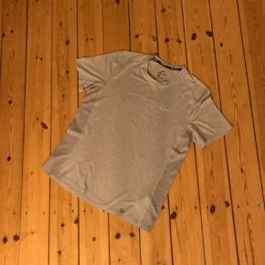 Lysegrå løbetrøje fra Nike Running i Dri-fit. Brugt en enkelt gang og vasket. Logoet samt en stribe bagpå er reflekterende. Mesh i begge sider 🌼
