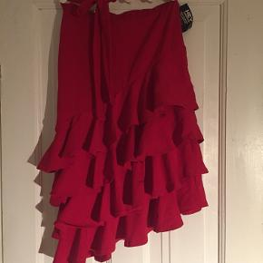 Fin rød nederdel i skråt snit med flæser og bindebånd i livet
