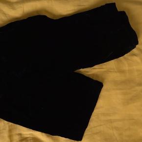 Sorte velour bukser, intet mærke da de er skræddersyet.  De er lidt store i str, men fede med et bælte.   Højtaljede, med pyntelomme bagpå, de er vide i benene.   Sry for dårligt lys på billederne, skriv hvis i vil have andre.   Kom gerne med bud!