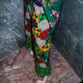 - BENYT 'KØB NU' FUNKTIONEN, VED KØB -  Unik gulvlang retro nederdel. Nederdelen har et multifarvet blomstret mønster og en grøn flæsekant forneden som matcher taljekanten øverst. Den lukkes med en diskret lille lynlås i venstre side med tilhørende knap øverst. Nederdelen har ingen stretch i, ej heller i taljen, men et tørklæde eller et bælte kan bruges til at holde den oppe, hvis taljemålet er for bredt.   ○ Mærke: Ukendt ○ Størrelse: Ukendt - Taljemål: 35 centimeter  - Bredde, midtpå: 56 centimeter - Bredde, nederst: 90 centimeter - Længde: 100 centimeter ○ Fit: Tætsiddende i taljen og løs A-form nedefter. Størrelsen er cirka omkring en str. S-M (se mål) ○ Stand: Brugt og vasket et par gange ○ Fejl/Mangler: Ikke umiddelbart ○ Materiale: Ukendt - intet indvendigt mærke