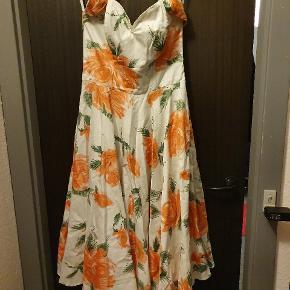 """50'er inspireret kjole fra britiske """"Vivien of Holloway"""". Kjolen har et rundskårent skørt med masser af vidde og egner sig perfekt med en petticoat under. Kjolen har store ferskenfarvede roser og ud over halterneck-funktionen, lukkes kjolen med en lynlås bagi. Derudover fungerer overdelen nærmest som en corsage, da der er stivere i den"""