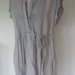 """Varetype: Tunika/skjortetop """"Hinano shirt"""" Farve: lyseblå   Sød sommerbluse/skjorte med læg og fine detaljer.   Str 40, løs model og stor i størrelsen  Har været lagt væk, derfor krøllet, men det kan stryges :-)  Brystvidde ca 2 x 55 Længde foran ca 77 cm, bagpå ca 84 cm  72 % bomuld, 28 % viscose  Let gennemsigtig  Jeg bytter ikke !  Byd gerne samlet på flere annoncer, så sparer du porto og jeg kan give dig rabat :-)  Jeg handler gerne Mobile Pay.   Oplyst porto er med DAO uden omdeling, dvs til pakkeshop.  Se mere om betaling og porto på min profil."""