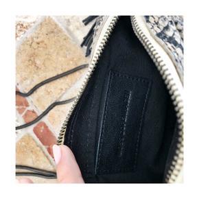 """Crossbody """"slangeskinds"""" taske i beige lakeret finish, fra Moss Copenhagen. Aldrig brugt.  Kom med et bud :)"""
