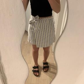 Sød hvid slå-om nederdel fra H&M med lyseblå striber og bindebælte i livet. Har kun være brugt få gange. Det er 21 % hør blanding, og den har lommer i siderne. Bæltet kan tages af.