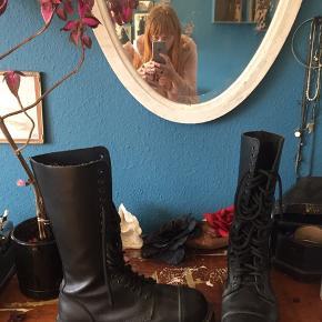 Ægte militærstøvler i sort kernekæder. Langskaftede Snørestøvler. Er virkelig robuste, og kan bruges både som efterårsstøvler, og vinterstøvler med en varm sok i. Kan også bruges som vandrestøvler.  Er kun brugt ca 5 gange og står næsten som nye uden skader eller slid.