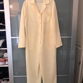 Lys gul buksedragt fra Reclaimed Vintage med grønne syninger. Kan sagtens passes af str 38.