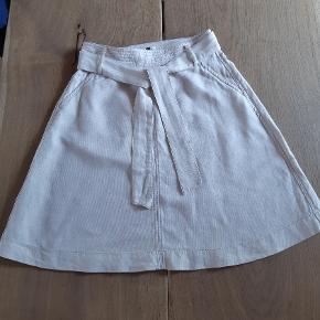 Sød nederdel med bindebånd. Lukkes med lynlås i taljen. Kun vasket, aldrig brugt. Farven er en lys sandfarvet.