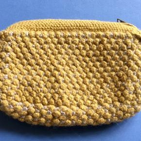 Fin clutch fra Aiayu . Udvendig er i pæn stand uden huller, pletter, fnuller eller lign. Kun et par skygger ved den ene kant i bunden. Indvendig bærer den præg af at være brugt som kosmetikpung, med pletter og mørkere området (intet det klistrer eller smitter af:-)). Ved ikke om det kan tages i en rens. Mål: 23 x16 cm. Søgeord: Aiayu cluth pung strikket strik gul sand knit knitted wallet purse bag Helen Babylama uld