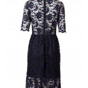 Fin blonde kjole i mørkeblå og sort fra Ganni. Der står L i mærket men passer også M. Lynlås i ryggen og elastisk stof der ikke strammer.