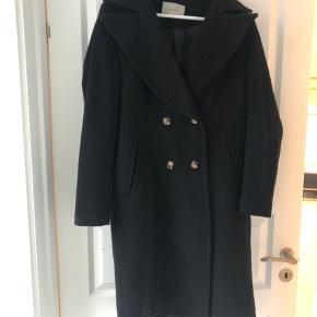 Fin og lang uldfrakke fra Gestuz.  Brugt 5-6 gange. Uden fejl og mangler.  Frakken er varm, og består af 50% uld.  «High tech thermo insulation»  «Maya coat».