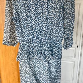 """Smuk kjole fra Ganni i mønstret blå/turkis og hvid farve.  Det er en str. L, men passes af M. Der er elastik i taljen ved skørtet/""""frill""""-effekten.  Kjolen er i rigtig god stand, da den kun er brugt enkelte gange.   Skal helst afhentes i København.  BYD gerne :)"""