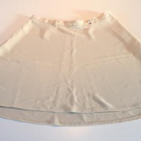 Beigefarvet nederdel i A-facon. Lidt længere bagpå end fortil. M/smalle bæltestropper.