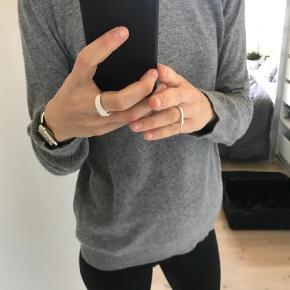 """Varetype: Bluse Farve: Grå Oprindelig købspris: 400 kr.  Bluse/trøje i 100% uld. Blusen har kun været brugt et par gange, men da der er en lille smule fnuller i nederst i venstre side, har jeg sat standen til """"god men brugt"""". Jeg er normalt en str s/m, så blusen er ikke stor i størrelsen (det er en large). Jeg vil mene, at den kan passe både en small, medium og large - afhængig af hvor stram man ønsker den.  Jeg bytter ikke. Jeg kan mødes i københavn og handle, hvis du vil spare fragten."""
