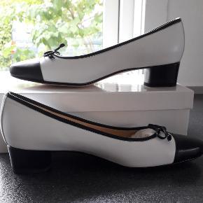 Brunate Smarte ballerinaer i hvide med blå snude, kanr og sjølfe Brunate er håndlavede sko i ypperligste kvalitet af 100 % læder Komplet med stofpose og i original æske. De ville normalt være angivet med prismærke, men  Dahlberg sko hvor jeg har købt dem sætter ikke mærke på skoene. Bemærk: det kan ses på sålen, at de er  prøvet i forretningen.  Mål: Længde 26 cm. Det bredeste sted på forsålen 8 cm. Hælhøjde 3,5 cm.
