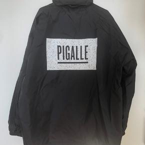 Pigalle regnjakke, sort, str. XL, med foldehætte gemt i nakken.   Brugt en enkelt gang.