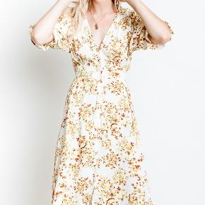 Rafa Midi dress by Faithfull the brand. Almost new.  White and floral pattern feminine dress.    It has a few buttons on the  front and a tie waist.   It's perfect for spring and summer.