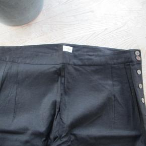 Sorte selskabsbukser af mærket Emily UK str 22. Bukserne knappes i siden, hvilket giver et elegant snit. Materiale: 55% bomuld - 42% viscose - 3% elastan Hel længde ca 106 cm.  Se også mine flere end 100 andre annoncer med bla dame-herre-børne og fodtøj