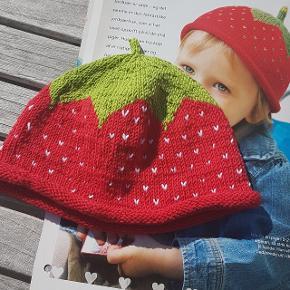 Håndstrikket jordbærhue, strikket i bomuldsgarn. Str. 6-12 mdr. Bredde 2*18,5 cm, højde fra toppen af hovedet ned til rullrkanten (mens den er rullet): 14,5. Målt med huen liggende fladt på bordet.
