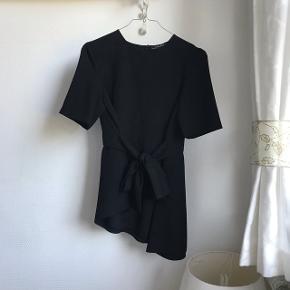 Nypris: 300,-  Eftertragtet t-shirt / top med bindebånd og asymmetrisk snit i bunden fra Zara Kan bindes på flere forskellige måder. ALDRIG BRUGT, da jeg ikke kan passe den 😕 Den er lidt stor til mig 🙈👎🏼 Virkelig lækkert/behageligt stof! Str. XS  🚭 Fra ikke-ryger hjem 🔁 Jeg bytter ikke. Sælger kun 📦 Køber betaler fragt 💁🏼♀️ Jeg kan mødes  Søgeord: populær - skævt snit