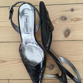 Flotte klassiske sorte sko fra Laura Camino med lille hæl i størrelse 37,5. Indvendig længde: ca.25cm. Hælhøjde: ca. 6,5 cm (hælen målt bagpå skoen). Skoene har aldrig været brugt. Oprindelig købspris: 1400kr.  Pris 450 kr. pp.