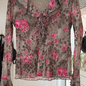 Sød blomstret bluse i 100% polyester med flæse detaljer. BM: 2x44cm Længde: 57cm Ærmer: 60cm Talje: 2x37cm