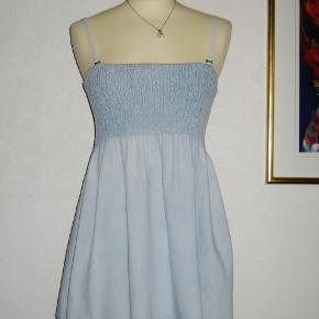 Rigtig sød kjole i tyndt lyseblå denim. Stropperne kan afmonteres så den bliver stropløs. Overdelen af kjolen er med elastik. Materialet er 100 % cotton. Str er S/M  Brystvidde: mellem 37-47 cm x 2 Længde: Målt fra øverst på overdelens kant til nederdelens nederste kant: 57 cm.  Ingen byt, og prisen er fast