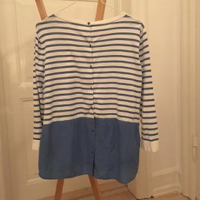 Smuk bluse med lyseblå striber og lyseblåt silkestykke nederst. Knapper bagpå. Str. M.