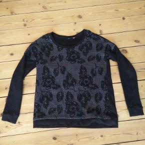 Fintstrikket sort trøje med grå-sort blomstermønster på forsiden. 88% bomuld/8% polyester/4% viskose.  Mål Længde: 68cm Bredde: 57cm  Kun brugt et par gange