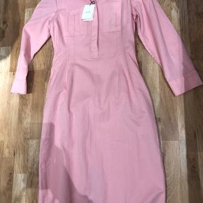 Brugt få timer. Prismærke medfølger.  Kjolen er som ny. 100% bomuld i smuk lyserød farve. 2 sidelommer. Brystlommer og knapper foran