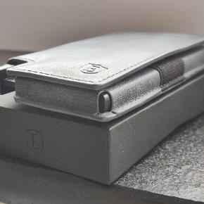"""Ekster 2.0 Parliament kortholder slim Premium leather   Farve: grå/blå Mål: L:11 B:6,5 H:2    Ny designet kortholder pung med, teknologisk RFID-beskyttelse, som blokere illegale skannere samt, identitetstyveri """"flise"""" regerer hvis du glemmer eller får din pung stjålet! Via en app samt selve """"flisen""""   Snavs og vandafvisende  Hurtigt adgang til kortene  Beauty age -læder Plads til 9 kort  Ubrugt, da gaven ikke var noget for min gamle far.   Mærket er kendt for deres kvalitet, design, samt identitetstyveri funktion.   Originale salgspris ligger mellem 680-780kr.    Søgeord:  Taske, tasker Diverse  Herre pung Herre smykke  Accessories  Tilbehør Wallet  Cardholder"""